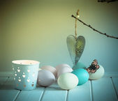 Eggs, candle and heart decoration — Stock Photo