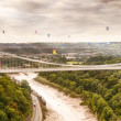 Hot air balloons behind suspension bridge — Stock Photo