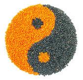 Orange and Black Lentil forming a yin yang symbol — Stock Photo