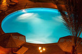 Nighttime setting of a luxury villa poolside — Stock Photo