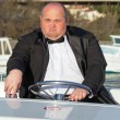 Overweight man in a tuxedo at the helm of a pleasure boat — Stock Photo