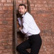 Stock Photo: Terrified mtrapped at top of ladder