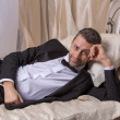 Stock Photo: Elegant playboy reclining on bed