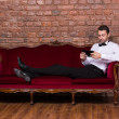 Stock Photo: Businessmlying on settee and reading tablet