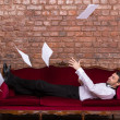 Stock Photo: Businessmlying on settee with flying papers