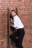 Terrified man trapped at the top of a ladder — Stockfoto