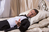 Elegant playboy reclining on a bed — Stock Photo