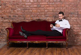 Businessman lying on a settee and reading tablet — Stock Photo