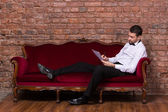 Businessman lying on a settee and reading paperwork — Stock Photo