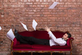 Businessman lying on a settee with flying papers — Stock Photo