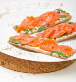 Saumon salé sur du pain croustillant au fromage et roquette — Photo