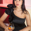 Woman with glass of brandy — Stock Photo