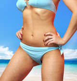 Woman in blue bathing suit — Stockfoto