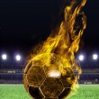Fiery soccer ball on field - Stock Photo