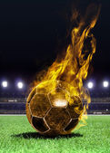 Fiery soccer ball on field — Stockfoto