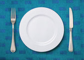 White plate knife and fork on table — Stock Photo