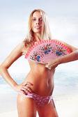 Woman holding fan on beach — Stock Photo