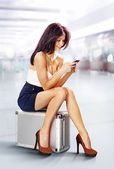 Traveler in airport with phone — Stock Photo