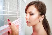Señora mirando a través de persianas — Foto de Stock
