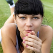 Sportswoman lies on green grass — Stock Photo