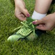 Stock Photo: Woman ties laces on green shoes