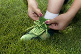 Woman ties laces on green shoes — Stock Photo