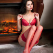 Stock Photo: Girl in red underwear sits near fireplace