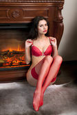 Girl in red underwear sits near fireplace — Stock Photo