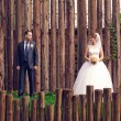 Bride and groom on wedding day on the background of a huge fence — Stock Photo