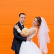 Wedding bride and groom on a bright orange background — Stock Photo