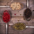 Peppercorns in silver spoons — Stock Photo