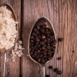 Salt and pepper in spoons — Stock Photo