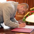 Stock Photo: Groom signing marriage form