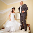 Bride and groom on the hotel bed — Stock Photo