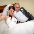 Bride and groom on the hotel bed — Stock Photo #12586636