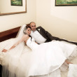 Bride and groom on the hotel bed — Stock Photo #12586688
