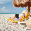 Stock Photo: Womwith laptop relaxing on deck chair