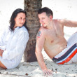 Couple sitting under palm tree — Stock Photo #12599074