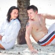 Couple sitting under palm tree — Stock Photo