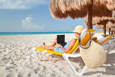 Woman with laptop relaxing on the deck chair — Stock Photo