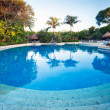 Dusk at tropical swimming pool — Stock Photo