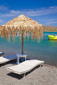 Deckchair under parasol at Aegean Sea — Stock Photo