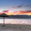 Постер, плакат: Parasol at Mirabello Bay at sunset