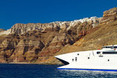 Boat at high volcanic cliff of Santorini island — Stock Photo