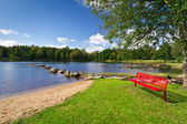 Red bench at the lake in Sweden — Stock Photo