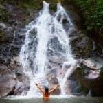 Woman refreshing herself in beautiful waterfall — Stock Photo #16330177