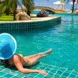Woman in hat relaxing at swimming pool — Stock Photo #16330521