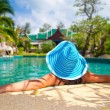 Woman in hat relaxing at swimming pool — Stock Photo #16330539