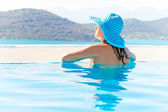 Woman in hat relaxing at swimming pool — Stock Photo
