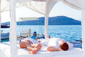 Relaxing on luxury white bed at the sea — Stock Photo